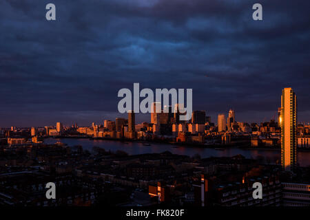 London, UK. 7th March, 2016. UK Weather: colourful evening sunset light reflected on London's Canary Wharf business - Stock Photo