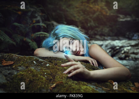 Beautiful dryad of the forest observing a magical butterfly . Fantasy and fairy - Stock Photo