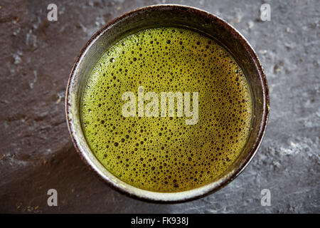 Green matcha tea with bubbles above view with whisk and powder and spoon - Stock Photo