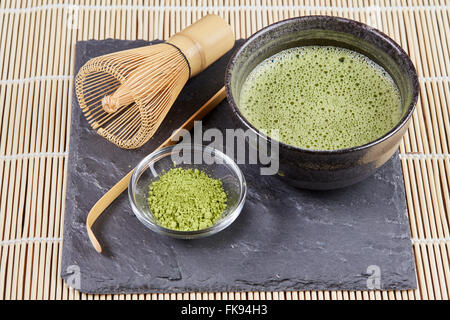 Green matcha powder and tea and whisk and spoon for preparation on black stone plate and white bamboo table mat - Stock Photo