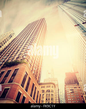 Retro toned photo of Manhattan buildings against sun, New York City, USA. - Stock Photo