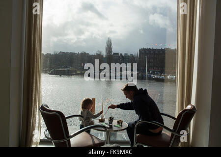 Father and daughter looking out a window in cafe in Amsterdam - Stock Photo