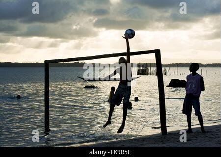 Boys playing ball on the seafront in Praia de Dentro - Peninsula de Marau - Stock Photo