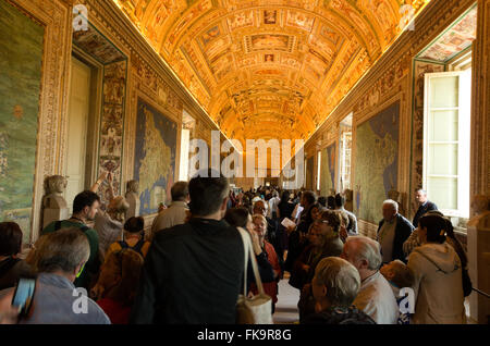 Large crowds of tourist traveling through the long hall with gold ceilings in Vatican Museum. - Stock Photo