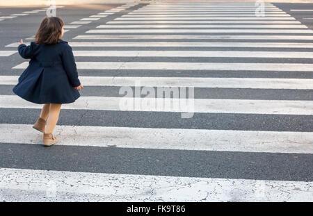 Little girl running and crossing alone a crosswalk. Dangerous behavior - Stock Photo