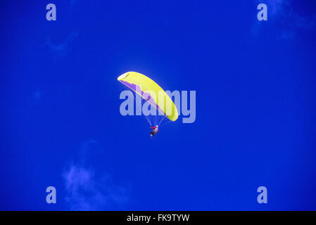 Man paragliding in colorful gear above Jackson Hole; Wyoming; USA - Stock Photo