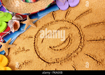 Smiling sun drawn in sand on a Mexican beach, with sombrero, straw hat, traditional serape blanket, starfish and - Stock Photo