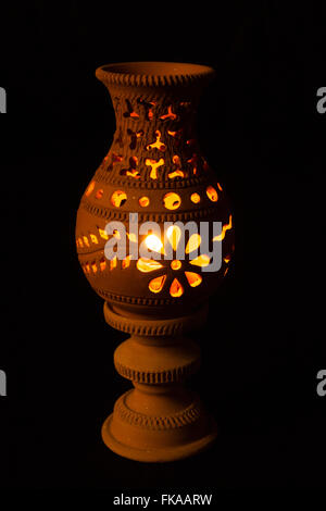 craft lamp with a lit candle inside on black background - Stock Photo