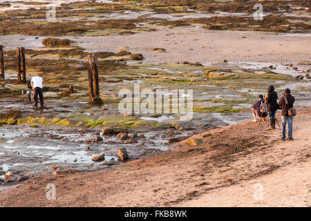 Photographers on the Rocks at St Mary's Island in the low evening warm light, Whitley Bay, Tyne and Wear, UK - Stock Photo