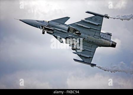 A Saab JAS 39C Gripen F 7, Swedish Air Force, Satenas, 39227, '227', takes off into an overcast sky at an airshow - Stock Photo