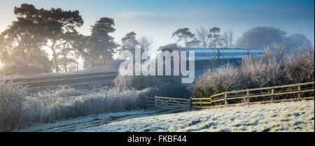 the train from Exeter to London Waterloo passing on a frosty morning at Milborne Wick, Somerset, England - Stock Photo