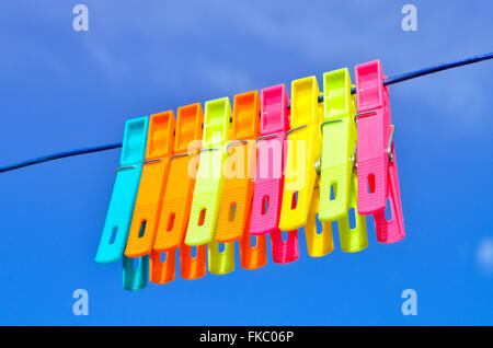 Plastic clothes pegs on washing line. - Stock Photo