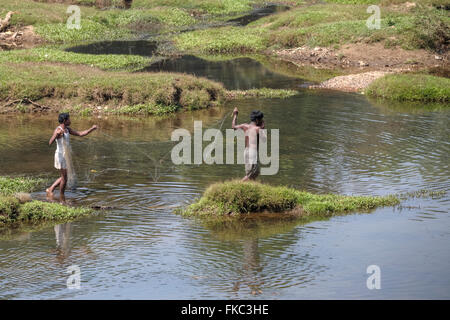 men fishing with a net in a river in Kerala, South India - Stock Photo