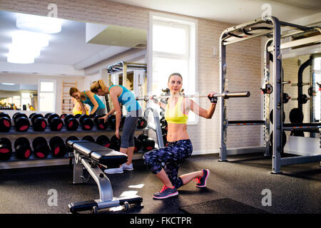 Women in gym exercising with weights and bar - Stock Photo