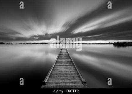 A small jetty on a lake near Amsterdam The Netherlands in black and white. A slow shutter speed was used to see - Stock Photo