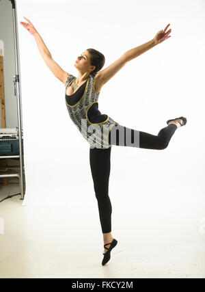 Young woman dancing against white background - Stock Photo