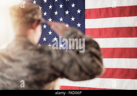 Soldier saluting American flag - Stock Photo