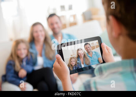 Boy (8-9) photographing family with digital tablet - Stock Photo