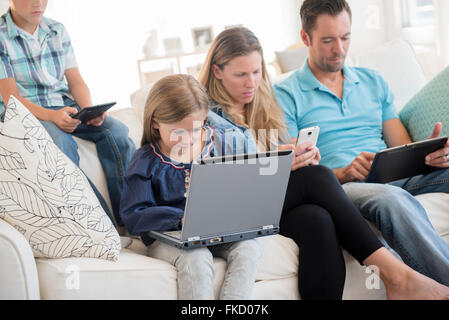 Family with two children (6-7, 8-9) sitting on sofa, using laptop and digital tablets - Stock Photo
