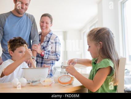 Family with two children (6-7, 8-9) preparing food - Stock Photo