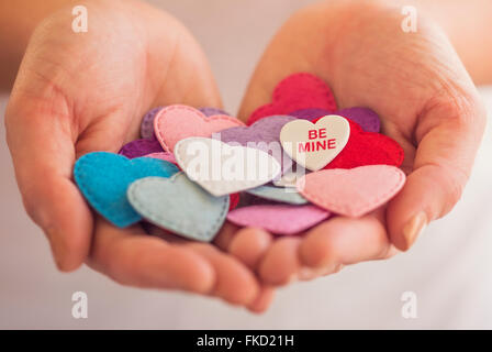 Close-up of woman's hands holding decorations in heart shape - Stock Photo