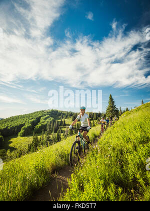 Parents with children (10-11,12-13, 14-15) during bike trip - Stock Photo
