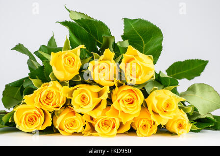 Bunch of fresh yellow roses lying flat on a white surface - Stock Photo