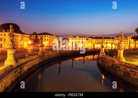 Illuminated Prato della Valle with statues at dusk - Stock Photo