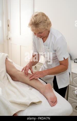 A masseuse massaging a woman client's leg massage - Stock Photo