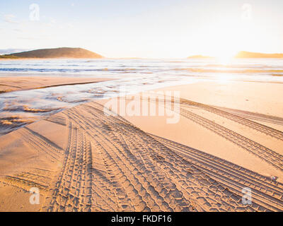 Tire tracks on beach at sunset - Stock Photo