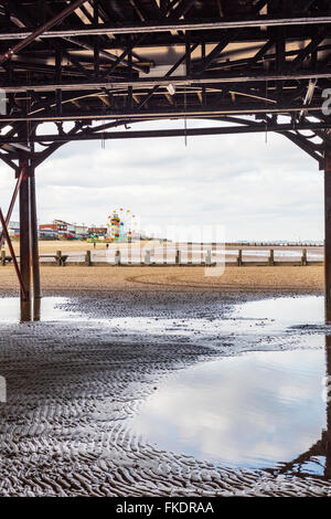 Cleethorpes UK beach coastline from under pier towards amusements seafront sea coast coastal town towns England - Stock Photo