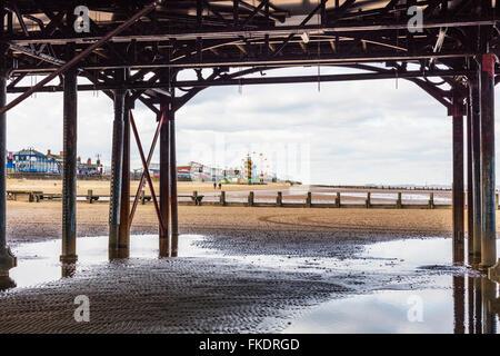 Cleethorpes UK beach coastline from under pier towards amusements seafront sea coast coastal town towns England - Stock Photo