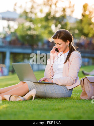 Businesswoman in park working on laptop, making phone call - Stock Photo