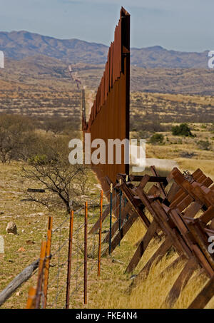 US border fence end Mexican side, with railroad rails extending the fence to prevent illegal vehicle travel to the - Stock Photo