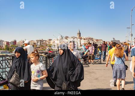 People walking and men fishing on Galata Bridge, Galata Tower in background, Istanbul, Turkey - Stock Photo