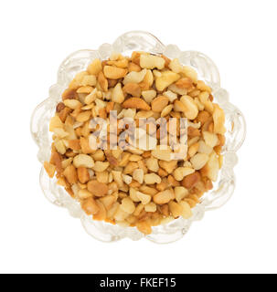 Top view of roasted and salted macadamia nut pieces in a glass bowl isolated on a white background. - Stock Photo