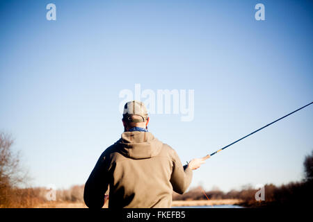 Fly fisherman casting off front of boat - Stock Photo