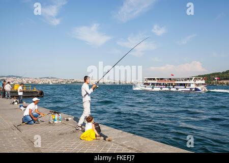 Men fishing on quayside, and passenger ferry passing, in the Bosphorus Strait, Istanbul, Turkey - Stock Photo