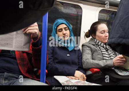 Woman sleeping in a  London underground train carriage, London UK - Stock Photo