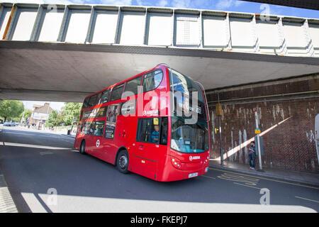 Red Routemaster bus going under railway bridge - Stock Photo