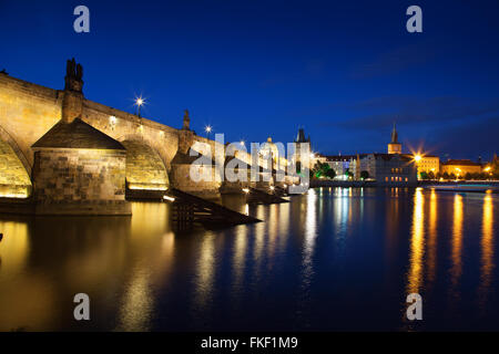 View at night across the Vltava River in Prague with Charles Bridge St Francis Church - Stock Photo