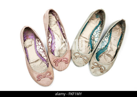 Above view studio shot of two pairs of pink and blue worn-out ladies shoes - Stock Photo