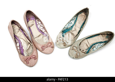 Above view studio shot of two pairs of pink and blue worn-out ladies shoes on white - Stock Photo