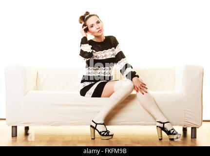 Fashion young woman in full length. Girl in fashionable striped dress high heels sitting on white couch. - Stock Photo