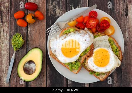 Healthy avocado, egg open sandwiches on a plate with cherry tomatoes on a rustic wood background - Stock Photo