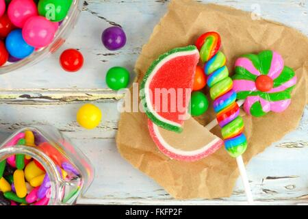 Assortment of sweet candies in a cluster on paper with rustic wood background - Stock Photo