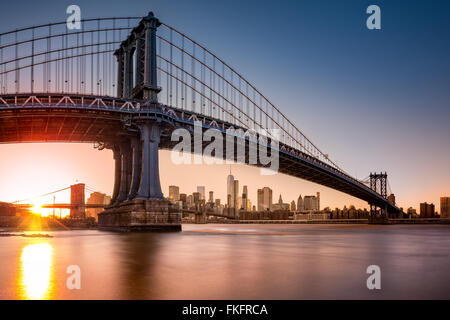 Manhattan Bridge framing New York skyline at sunset. - Stock Photo