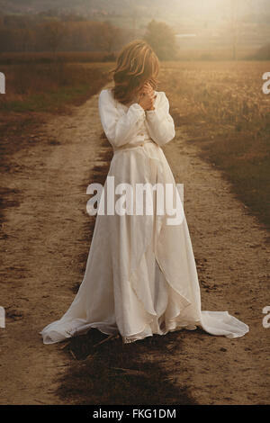 Lone woman with vintage bride dress in countryside . Purity and innocence - Stock Photo