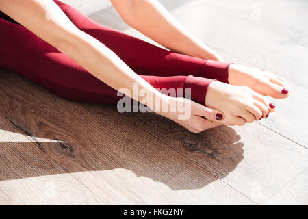 Closeup of slim legs of young woman gymnast sitting and stretching on wooden floor - Stock Photo
