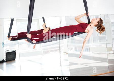 Focused beautiful young woman doing antigravity yoga in studio - Stock Photo